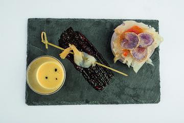 Láminas de bacallau sobre cama de vitelotte e salmorejo de cítricos